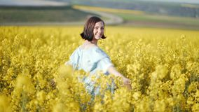 Portrait of happy woman in blue dress unexpectedly pops up with open arms among yellow canola flowers in field stock footage
