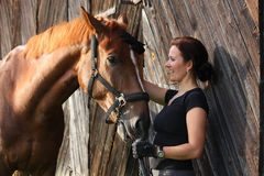 Portrait of happy woman and brown horse stock image