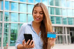 Portrait of a happy woman buying online with a smart phone and showing her credit card outdoors royalty free stock photography