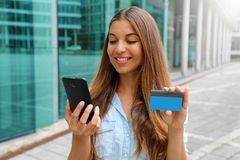 Portrait of a happy woman buying online with a smart phone and showing her credit card outdoors stock image