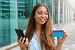 Portrait of a happy woman buying online with a smart phone and showing her credit card outdoors stock photos