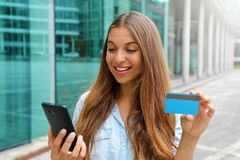 Portrait of a happy woman buying online with a smart phone and showing her credit card outdoors stock images