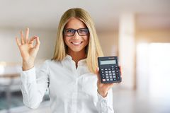 Woman with calculator in business center royalty free stock image