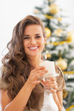 Portrait of happy woman with candle in front of christmas tree Stock Photography