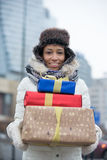 Portrait of happy woman carrying stacked gifts during winter Stock Images