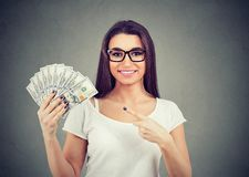 Portrait of a happy woman in casual clothing holding fan of money stock image