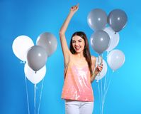 Portrait of happy woman with champagne in glass party balloons on color background. Portrait of happy woman with champagne in glass and party balloons on color stock image
