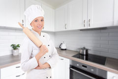 Portrait of happy woman in chef uniform with wooden baking rolli Stock Photography
