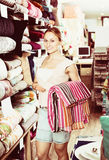 Portrait of happy woman choosing blanket. In bedding section in shop Royalty Free Stock Images