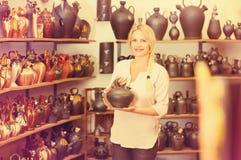 Portrait of happy woman choosing ceramic utensil Stock Photo