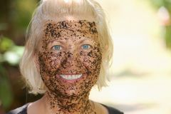 Portrait of happy woman with a coffee pilling mask Royalty Free Stock Image