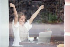 Portrait of happy woman in coffee shop celebrating success with Royalty Free Stock Photo