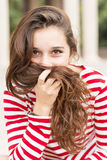 Portrait of happy woman covers her face with hair, hairstyle con Stock Image