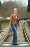 Portrait of a happy woman crossing train tracks with bag Stock Photo