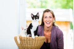 Portrait of happy woman with cute kittens in wicker basket Stock Photos