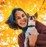 Portrait of happy woman with dog outdoors in autumn Stock Photo
