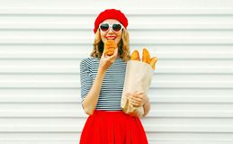 Portrait happy woman eating croissant holding paper bag with lon. G white bread baguette, wearing red beret on white wall background royalty free stock image