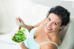 Portrait of happy woman eating salad Stock Photo