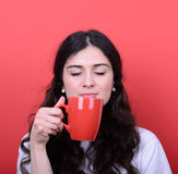 Portrait of happy woman enjoying cup of coffee against red backg Stock Photo