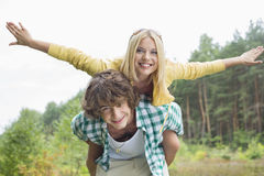 Portrait of happy woman enjoying piggyback ride on man in forest Stock Photos