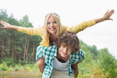 Portrait of happy woman enjoying piggyback ride on man in forest Stock Images