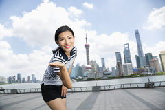 Portrait of happy woman gesturing while standing on promenade against Pudong skyline Royalty Free Stock Photography