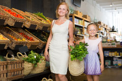 Portrait of happy woman and girl buying greens Royalty Free Stock Photo