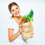 Portrait of happy woman with green vegan food in paper bag. Stock Image