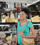 Portrait Of Happy Woman In Grocery Store. Portrait of happy young women in grocery store with salesman in background Royalty Free Stock Photo