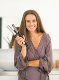 Portrait of happy woman with hair straightener Royalty Free Stock Photo