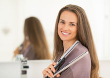 Portrait of happy woman with hair straightener Royalty Free Stock Image