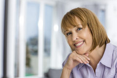 Portrait of happy woman with hand on chin at home Royalty Free Stock Image