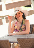 Portrait of happy woman in hat posing at cafe behind table Royalty Free Stock Images