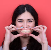 Portrait of happy woman with healthy smile holding denture again. This image is made in studio with model standing against colored backgrounds.Set of various Royalty Free Stock Photo