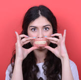 Portrait of happy woman with healthy smile holding denture again. This image is made in studio with model standing against colored backgrounds.Set of various Royalty Free Stock Image
