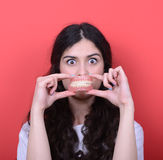 Portrait of happy woman with healthy smile holding denture again. This image is made in studio with model standing against colored backgrounds.Set of various Royalty Free Stock Photography