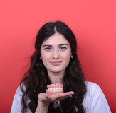 Portrait of happy woman with healthy smile holding denture again. This image is made in studio with model standing against colored backgrounds.Set of various Royalty Free Stock Photos