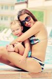 Portrait of happy woman and her sun in pool Stock Images