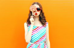 Portrait happy woman hiding her eye with lollipop, blowing red lips, wearing colorful striped dress on orange. Wall background royalty free stock photo