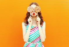 Portrait happy woman hiding her eyes with two lollipop, blowing red lips, wearing colorful striped dress on orange wall. Background royalty free stock photos