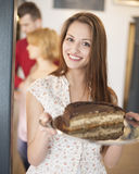 Portrait of happy woman holding cake in tray with friends in background at cafe Stock Images