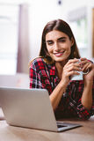 Portrait of happy woman holding coffee mug with laptop Royalty Free Stock Photos