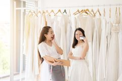 Portrait of happy woman holding credit card in wedding dress store owner,Beautiful successful dressmaker in shop and small busines stock photos