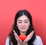 Portrait of happy woman holding heart in hands against red backg Royalty Free Stock Image