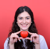 Portrait of happy woman holding heart in hands against red backg Royalty Free Stock Images