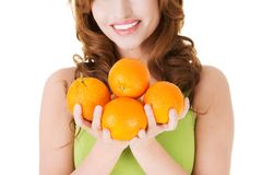 Portrait of a happy woman holding oranges Stock Photos