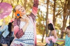 Portrait of happy woman holding pinwheel at campsite Stock Photo