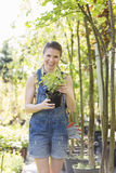 Portrait of happy woman holding potted plant at garden Stock Image