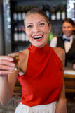 Portrait of happy woman holding a tequila shot in front of bar counter Stock Photography