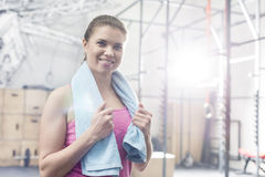 Portrait of happy woman holding towel around neck in crossfit gym Stock Photos